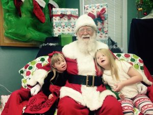Santa with two small girls on his lap.