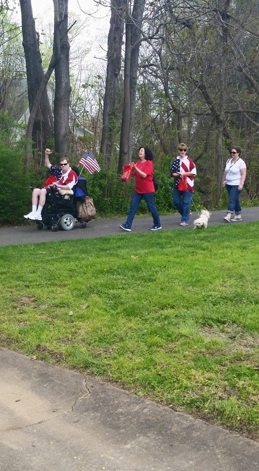 People on a walk with man in wheelchair