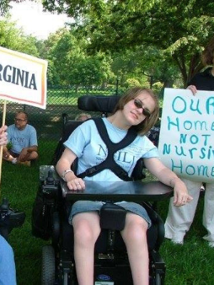 Young lady in wheel chair with sign that says 'Our Home Not Nursing Home'